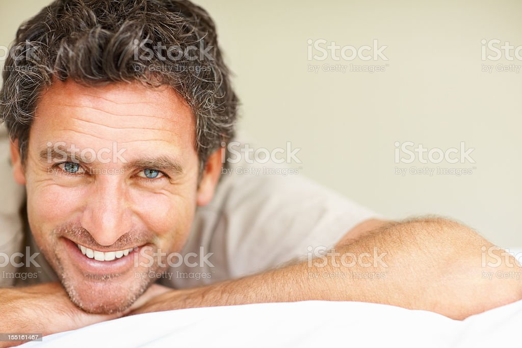 Smiling man on bed royalty-free stock photo