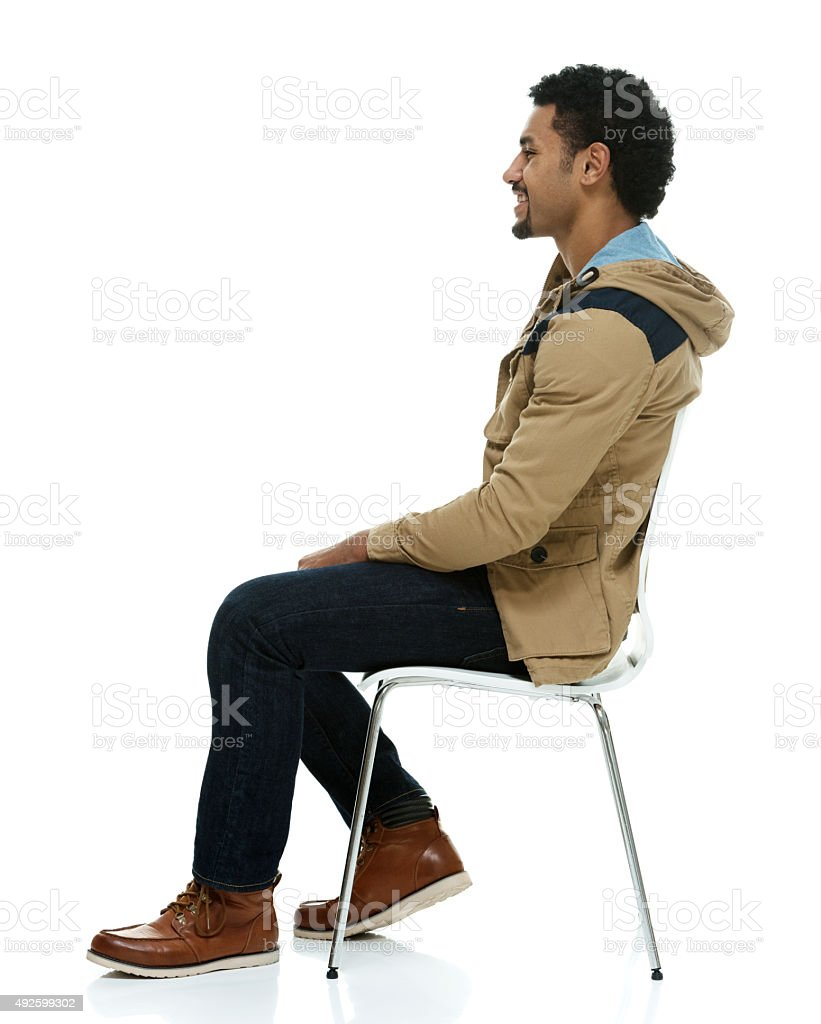 Smiling man on chair and looking away stock photo