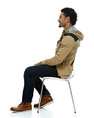 Smiling man on chair and looking away