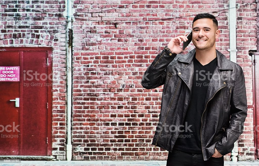Smiling man on phone in front of brick wall stock photo