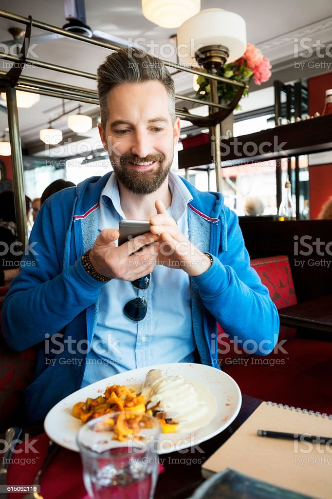 Smiling man photographing food while sitting at restaurant stock photo
