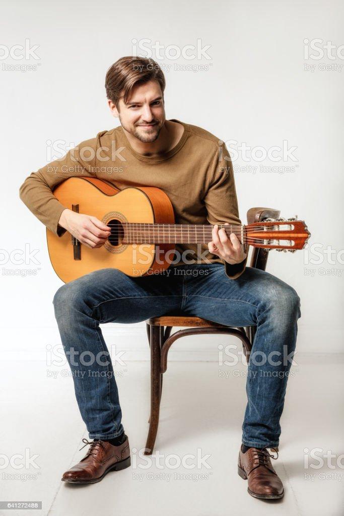 smiling man playing guitar stock photo