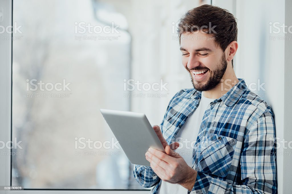 Smiling man playing on digital tablet stock photo
