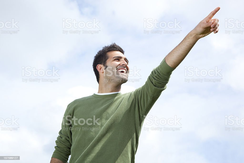 smiling man pointing to the sky - outdoors royalty-free stock photo
