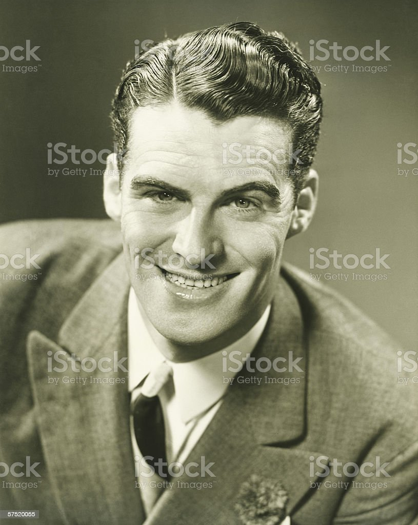 Smiling man posing in studio, (B&W), close-up, portrait stock photo