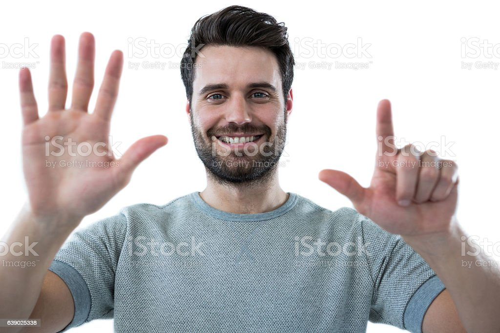 Smiling man pretending to touch an invisible screen stock photo