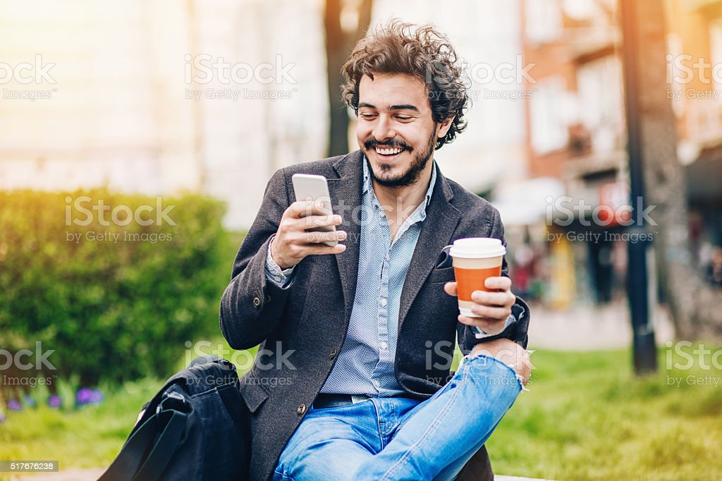 Smiling man reading a message stock photo