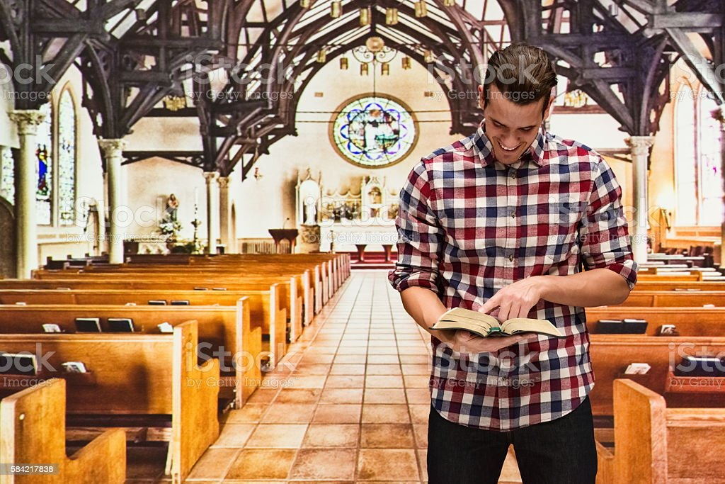 Smiling man reading bible in church stock photo