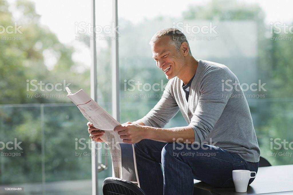 Smiling man reading newspaper royalty-free stock photo