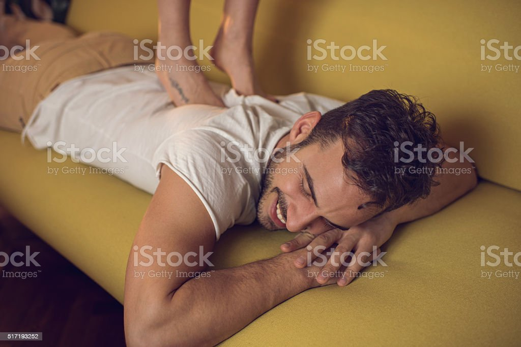 Smiling man receiving back massage on sofa at home. stock photo