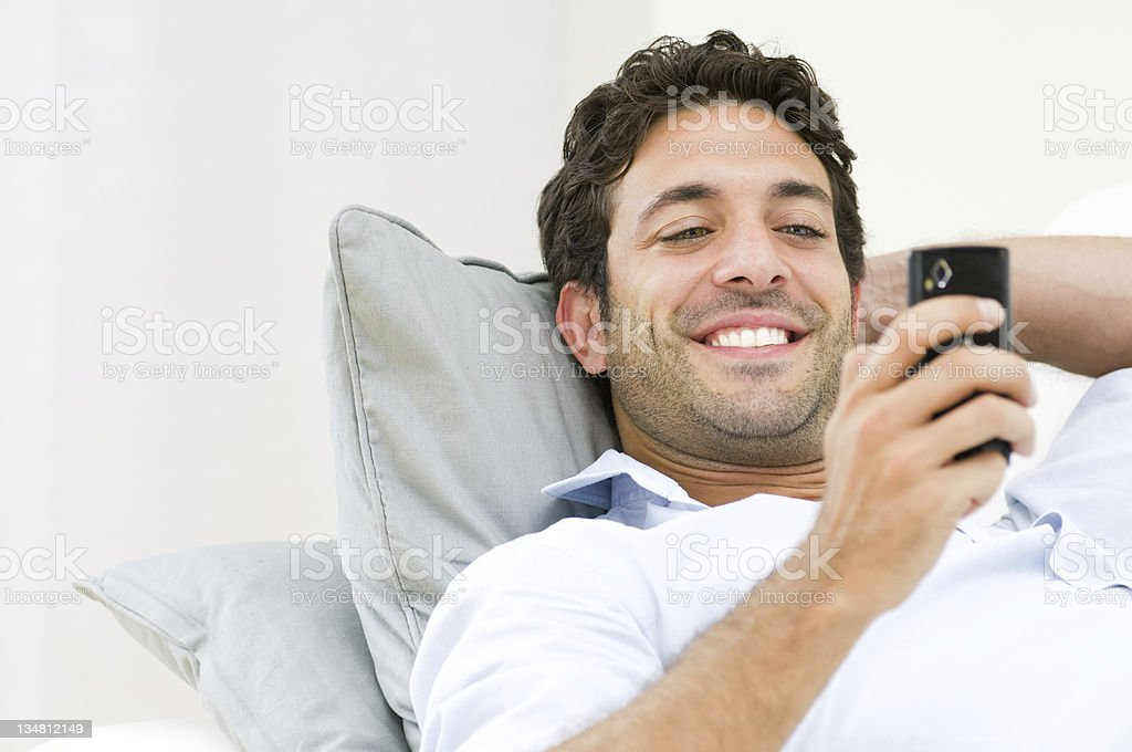 Smiling man relaxing and using mobile phone royalty-free stock photo
