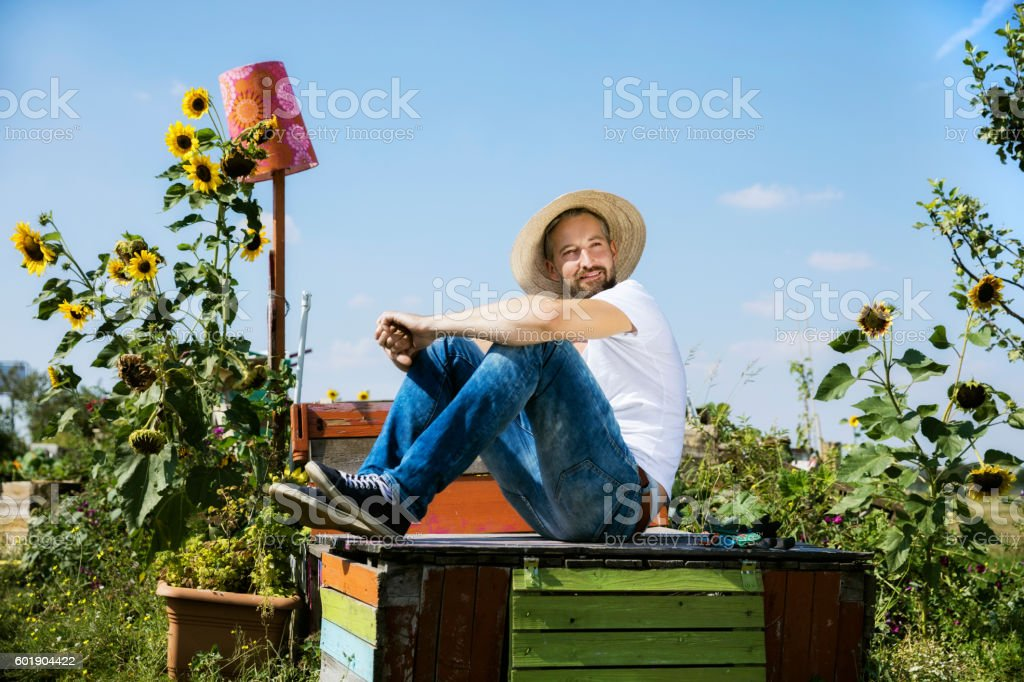 Smiling man resting on abandoned wooden table in garden stock photo