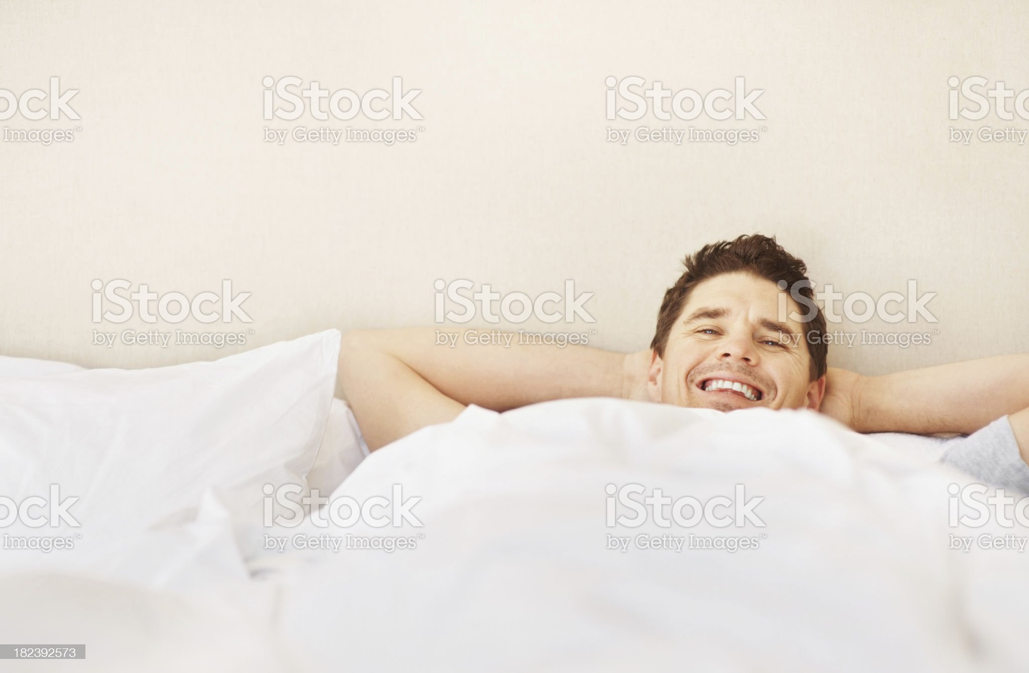 Smiling man resting on bed royalty-free stock photo