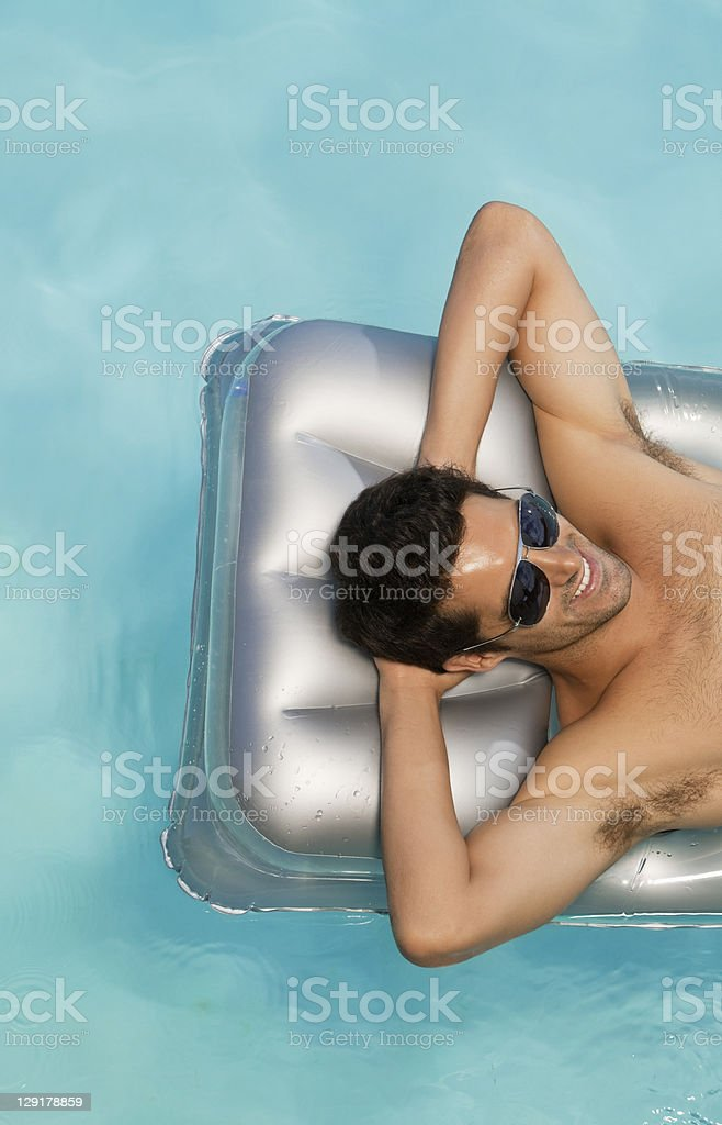 Smiling man resting on raft in swimming pool royalty-free stock photo
