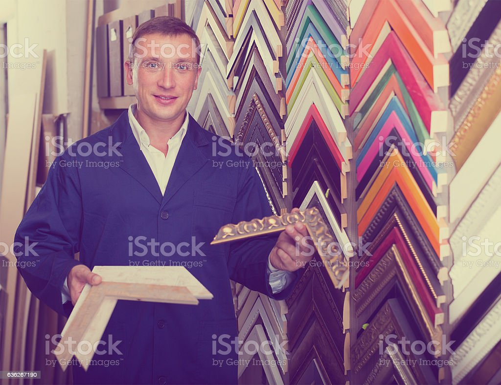 Smiling man seller in picture framing studio with wooden details stock photo