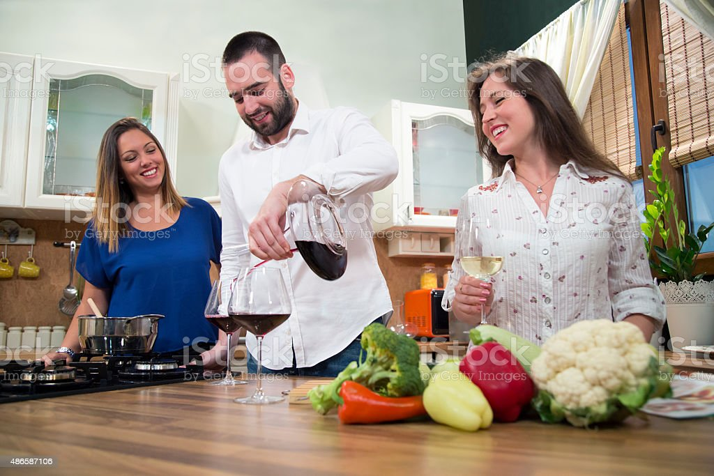 Smiling man serving wine to his female friends. stock photo