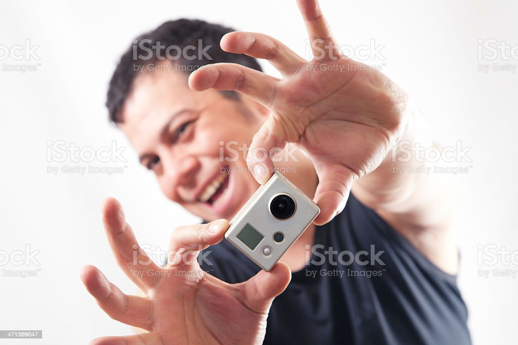 Smiling man shooting with a mini camera stock photo