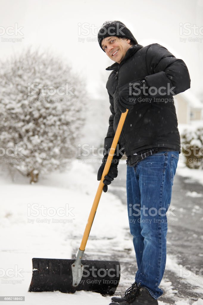 Smiling Man Shoveling Snow stock photo