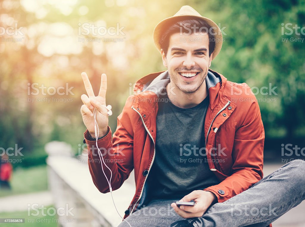 Smiling man showing the peace sign stock photo