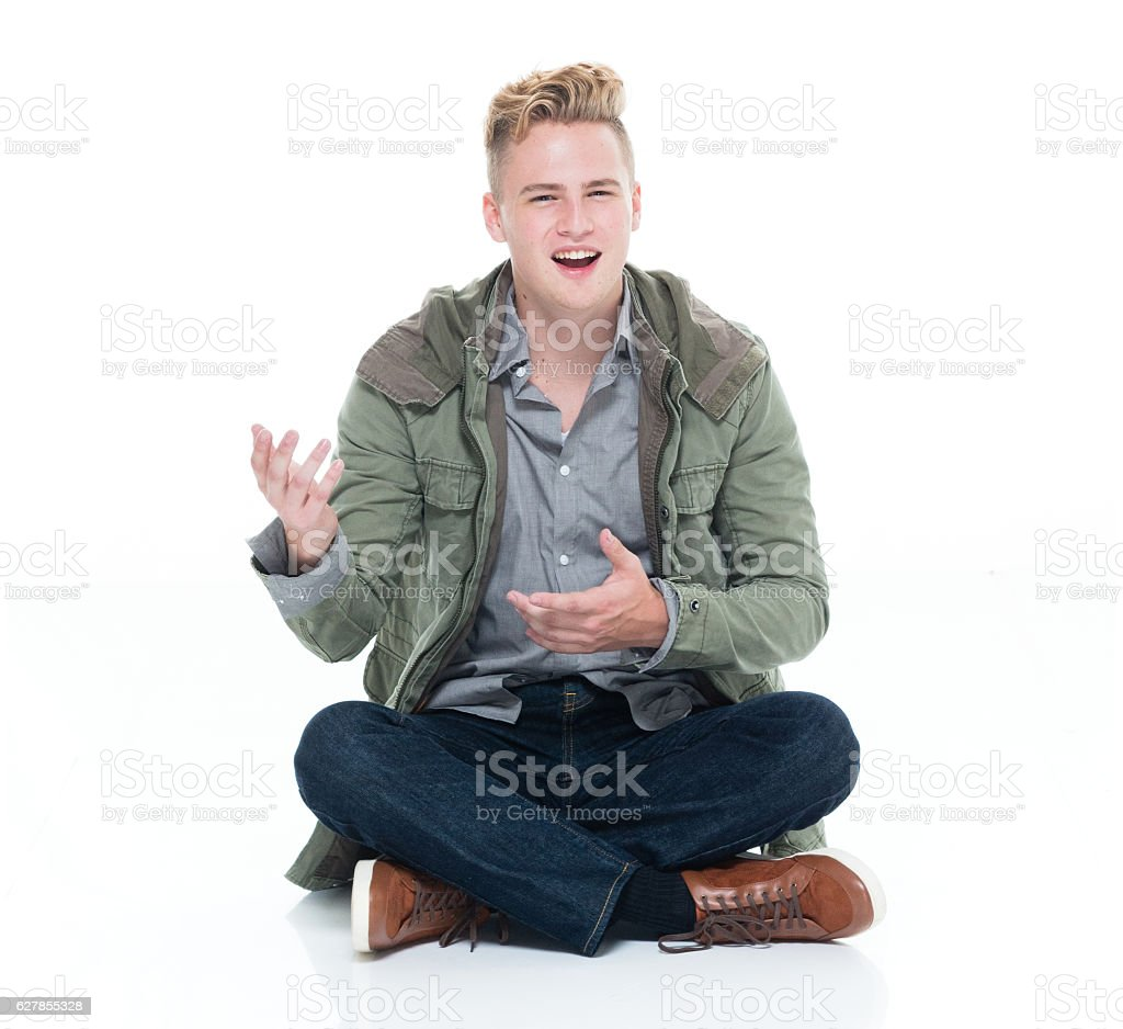 Smiling man sitting on floor and presenting stock photo