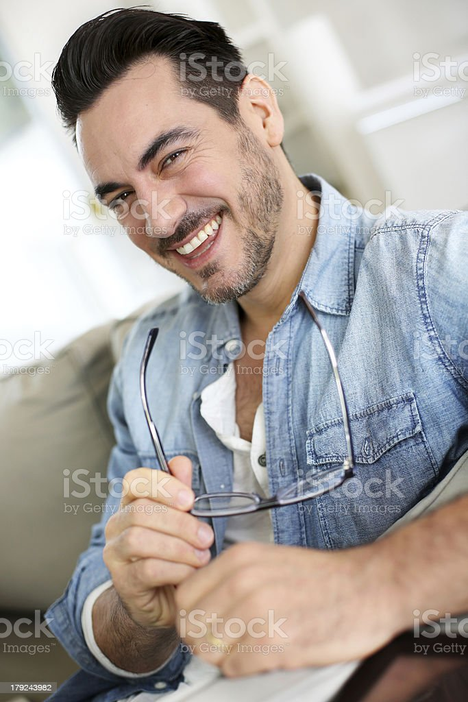 Smiling man sitting on sofa with eyeglasses in hands royalty-free stock photo