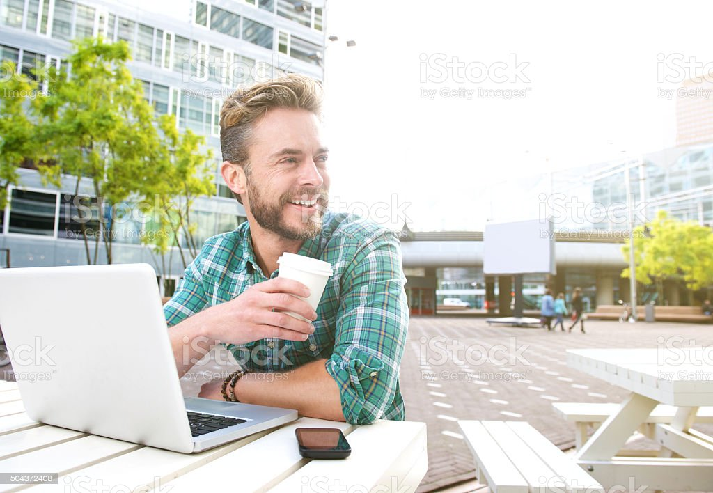 Smiling man sitting outside with laptop and coffee stock photo