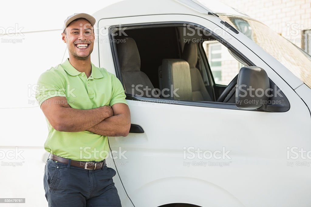 Smiling man standing against delivery van stock photo