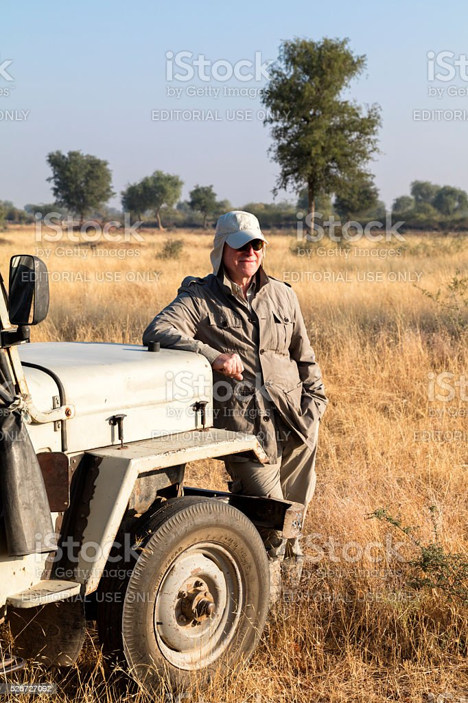 Smiling man standing by jeep during safari, Rajasthan, India stock photo