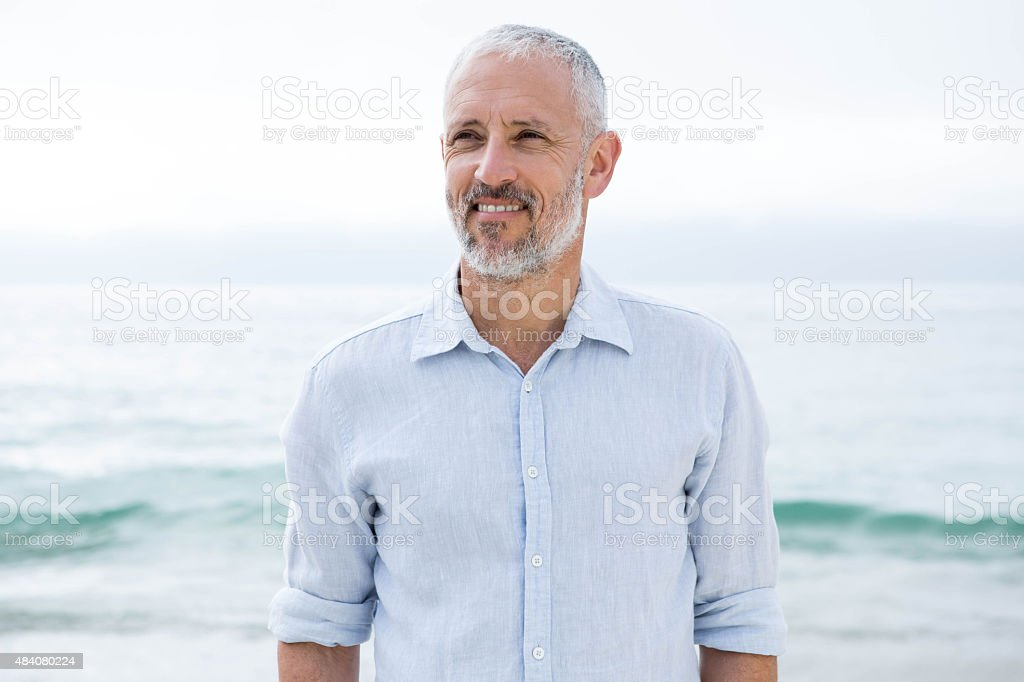 Smiling man standing by the sea stock photo