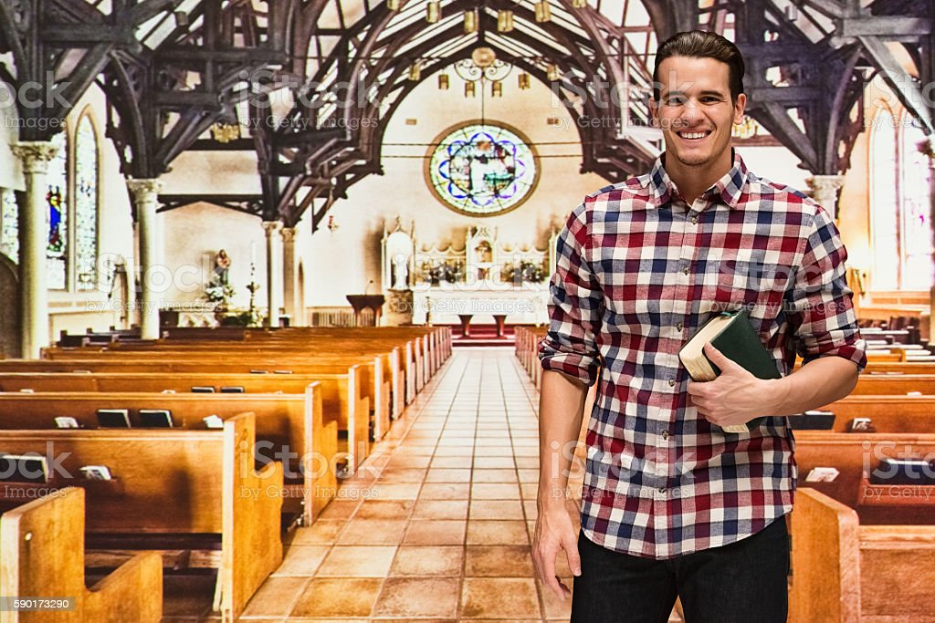 Smiling man standing in church stock photo