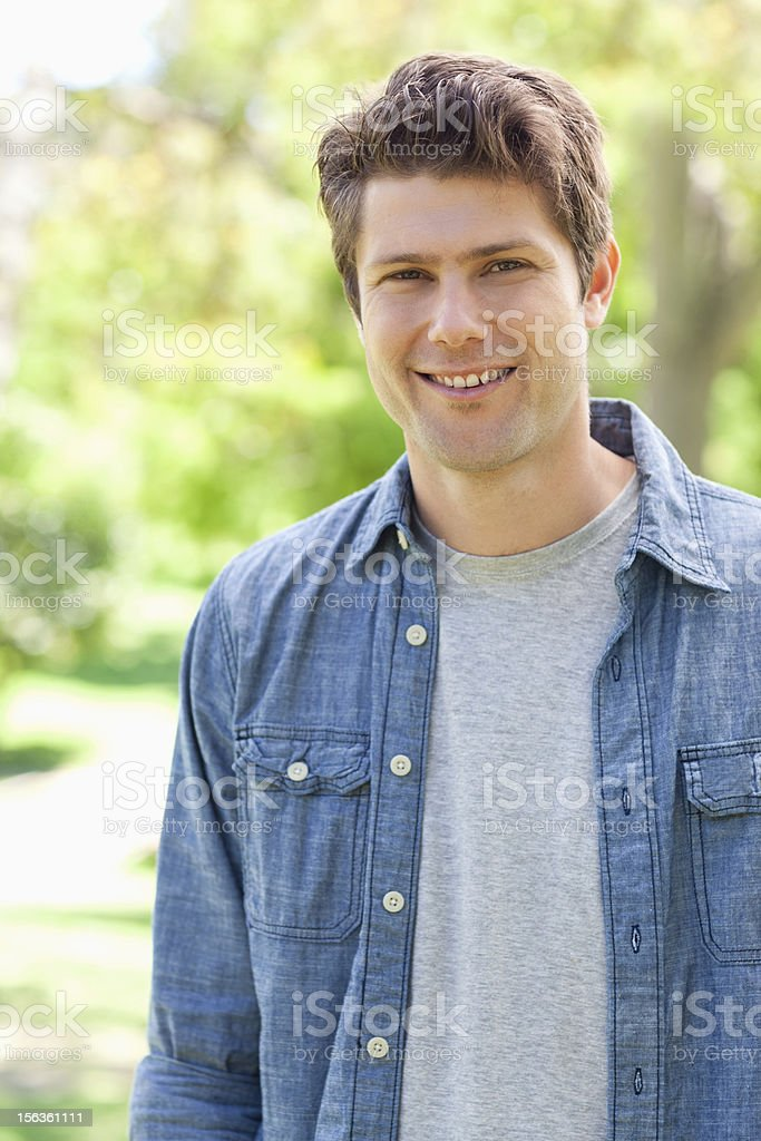 Smiling man standing in the park royalty-free stock photo