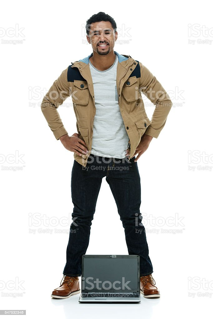 Smiling man standing with laptop stock photo