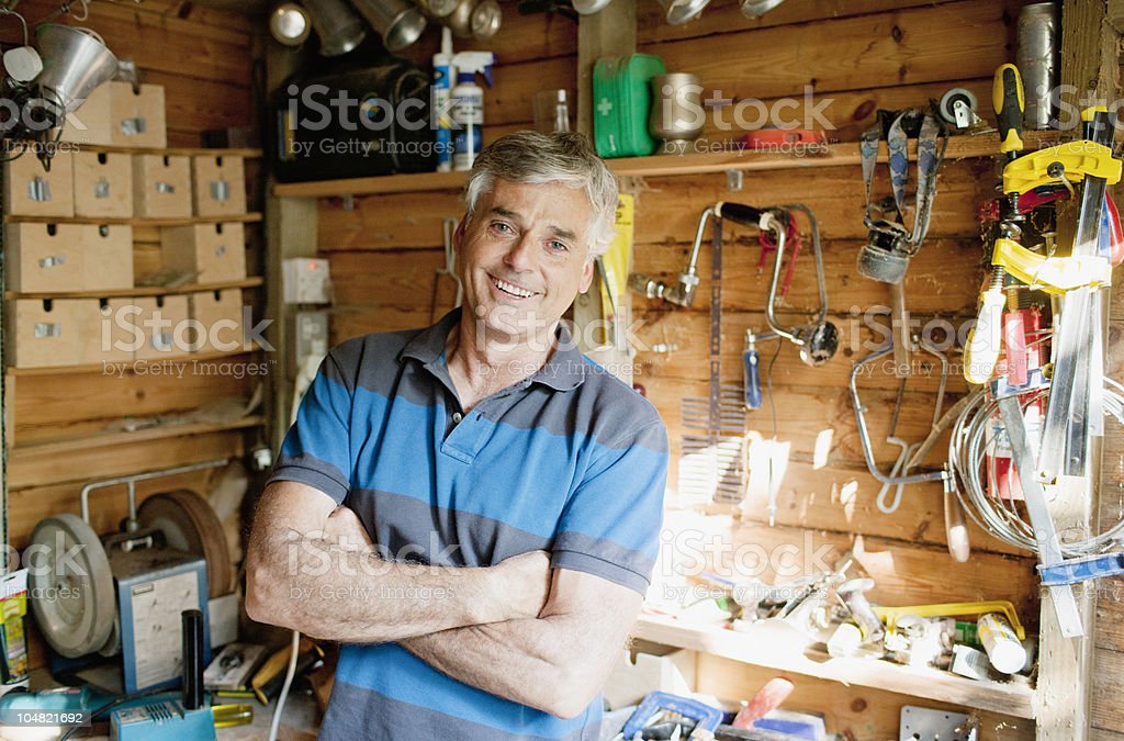 Smiling man surrounded by tools in workshop stock photo