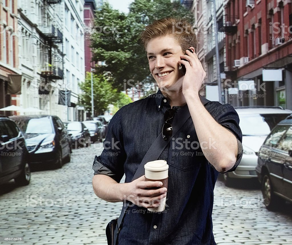 Smiling man talking on mobile phone with coffee cup royalty-free stock photo