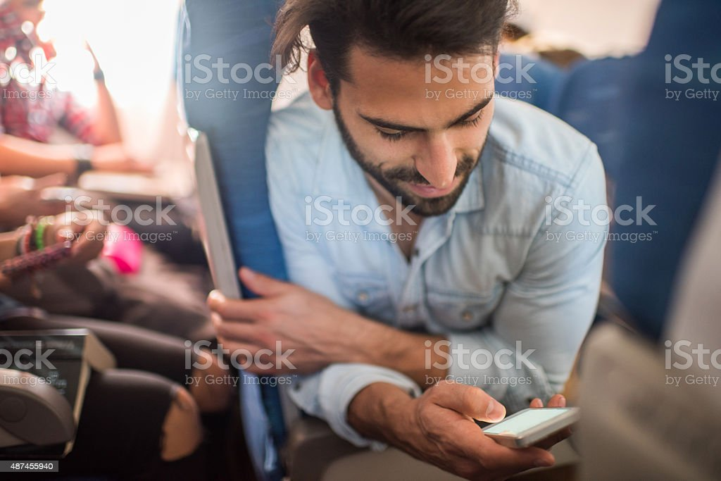 Smiling man travelling by airplane and using smart phone. stock photo