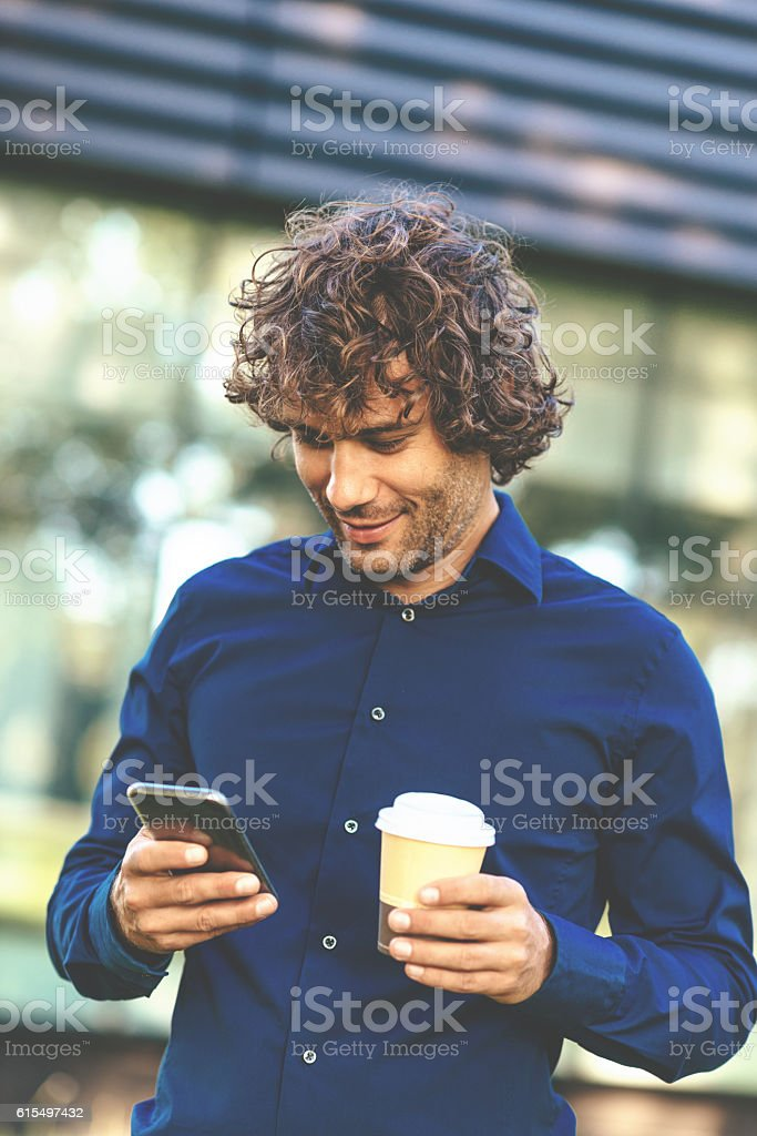 Smiling man typing message on phone stock photo
