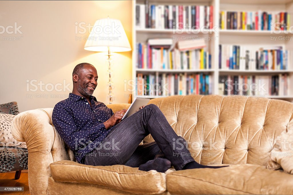 A smiling man using a digital tablet on his sofa stock photo