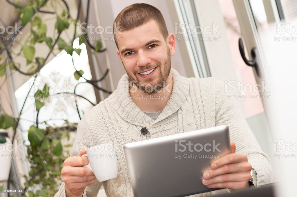 Smiling man using digital tablet at cafe stock photo