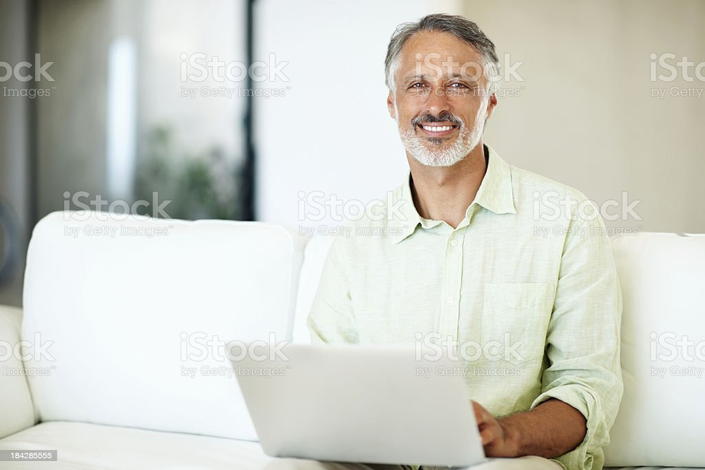 Smiling man using laptop at home royalty-free stock photo