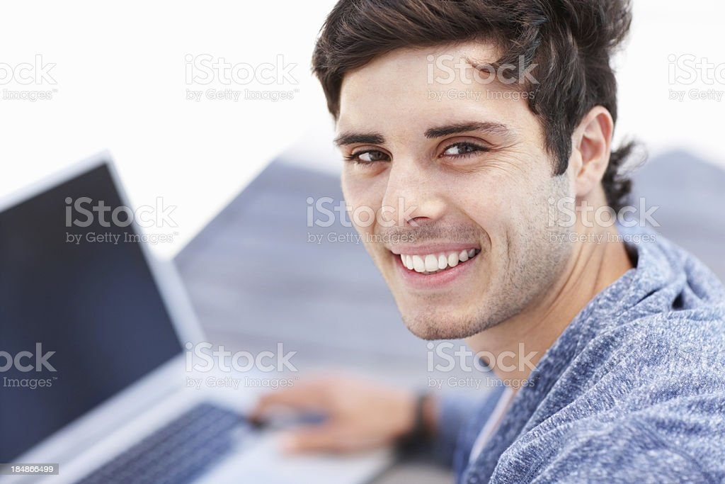 Smiling man using laptop outdoors royalty-free stock photo