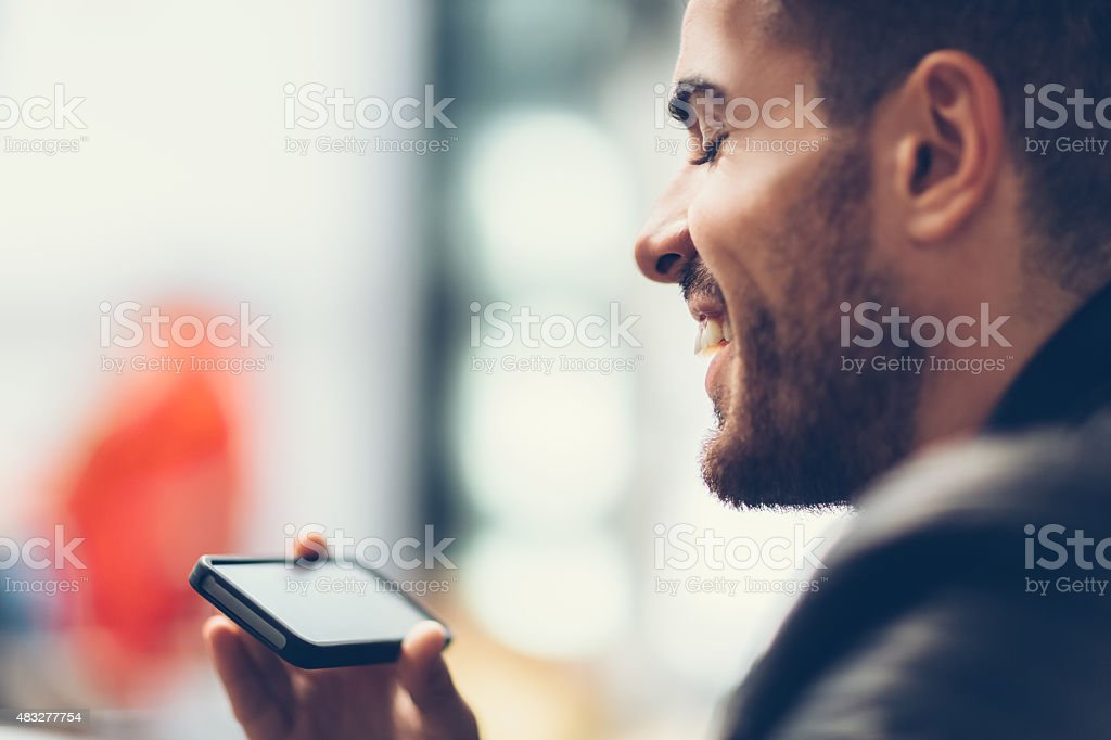 Smiling man using smartphone to watch tv stock photo