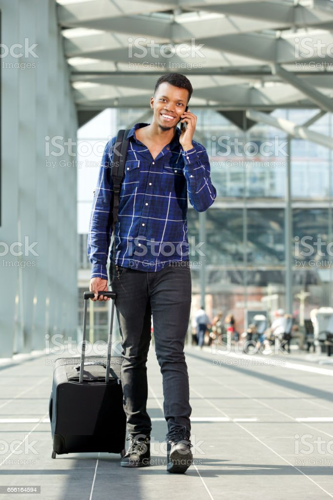 Full length portrait of smiling man walking with suitcase talking on...
