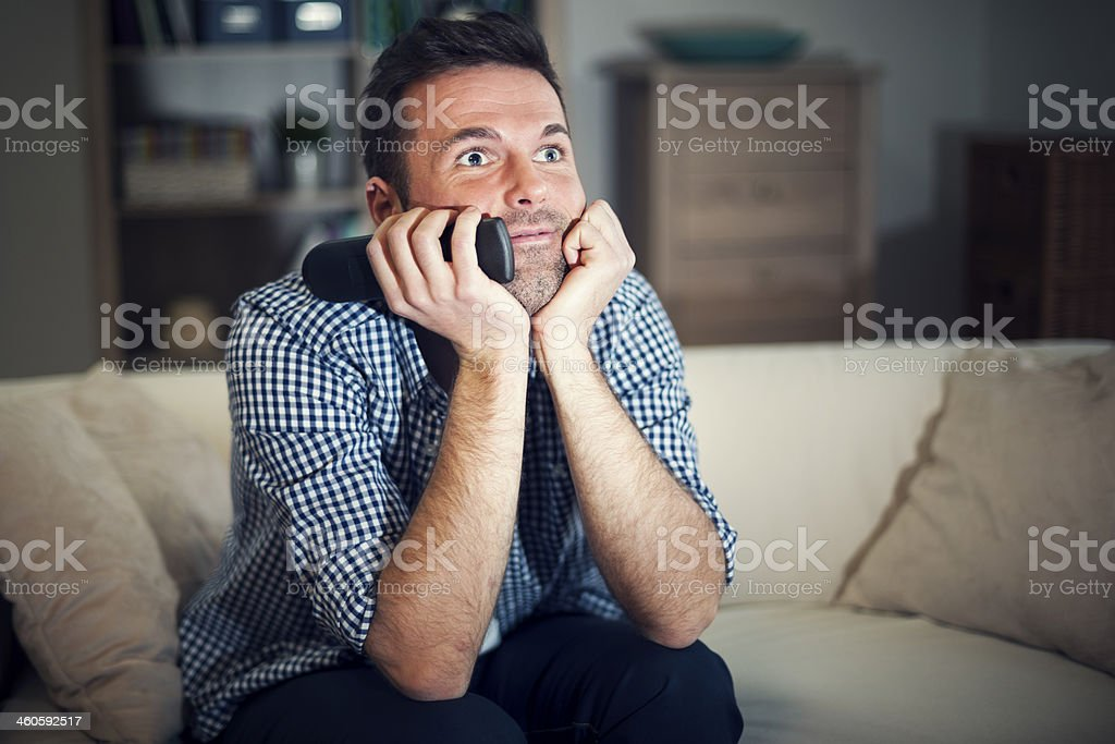 Smiling man watching interesting movie stock photo