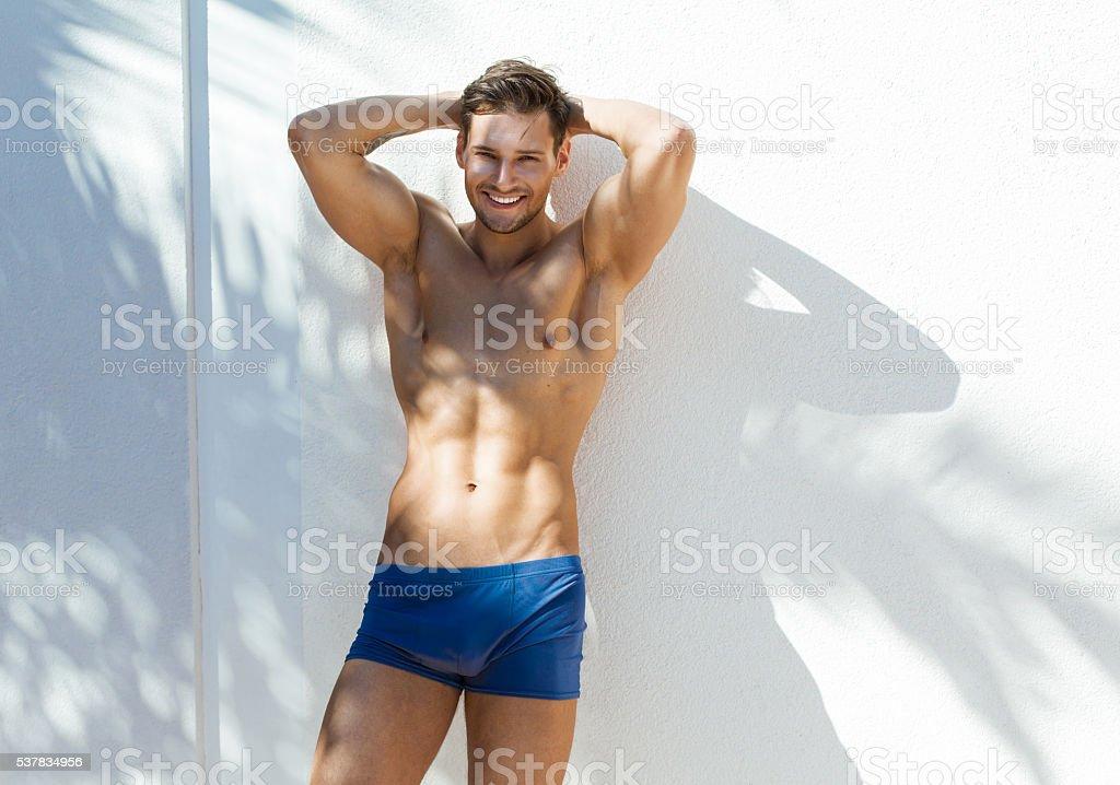 Smiling man wearig blue swimming trunks stock photo