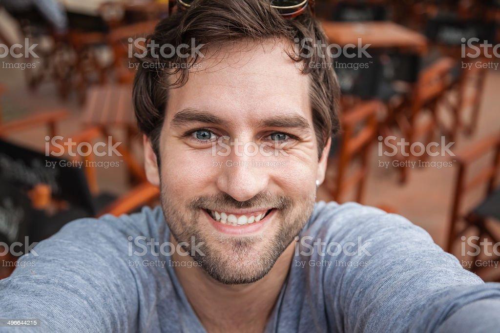 Smiling man wearing gray shirt taking a selfie stock photo