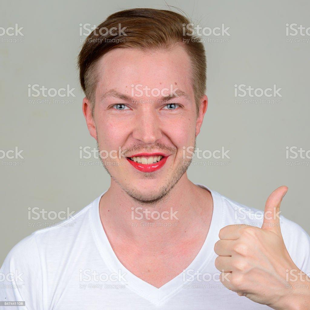 Smiling man wearing make up giving thumbs up stock photo