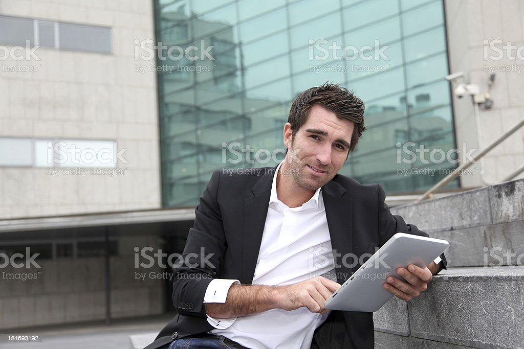 Smiling man websurfing in front of building and using tablet royalty-free stock photo