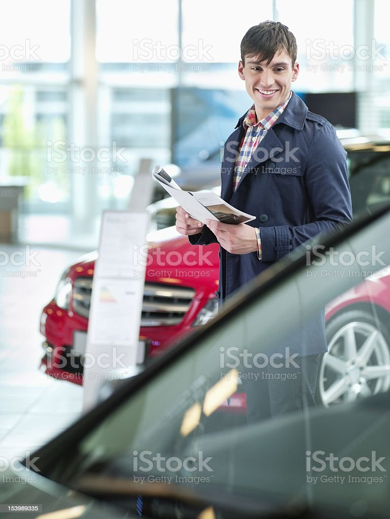 Smiling man with brochure looking at car in car dealership showroom royalty-free stock photo