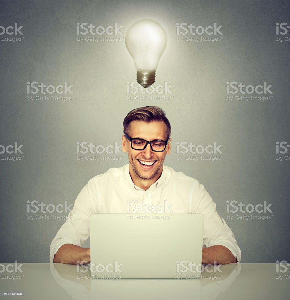 Smiling man with computer light bulb over head stock photo