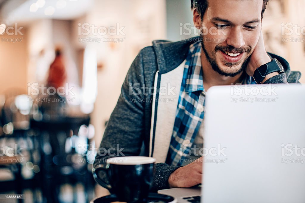 Smiling man with computer stock photo